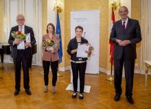 Drei Preisträgerinnen mit Urkunde und Blumen und der Wissenschaftsminister in einem prunkvollen Saal des Ministeriums