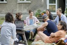 sieben junge Menschen sitzen an einem Tisch vor einem Wohnhaus und reden